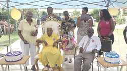 Violet Eversly (front left) sits in her yellow dress as church members and family celebrate her 100th birthday. She sits next to her brother Charley Mack who recently turned 95. The celebration was held at the Christiansted Seventh-day Adventist Church premises in St. Croix, on Aug. 22, 2021. [Photo: Royston Philbert]