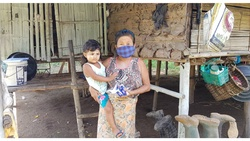 A mother holds her son as she receives hygiene materials, one of several items distributed in the community. [Photo Credit: Wa Wa Win/ADRA in Thailand]