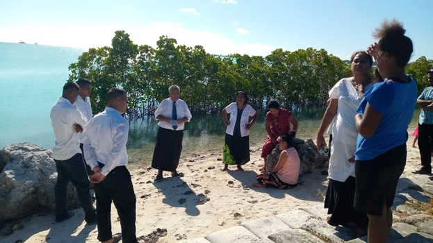 The baptismal candidates standing at the edge of the blue lagoon. [Photo Courtesy of Adventist Record]