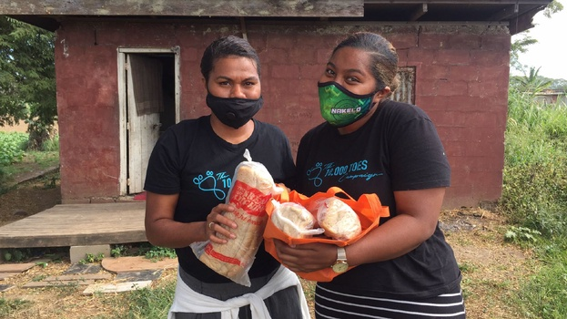 Milika and Luisa, ambassadors for 10,000 Toes, are ready to deliver bread into the house behind. [Photo Courtesy of Adventist Record]