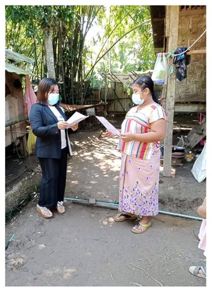 An ADRA volunteer reads through a handout about proper handwashing with a migrant worker. [Photo Credit: Wa Wa Win/ADRA in Thailand]