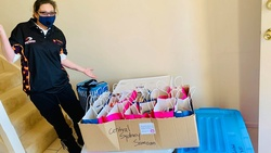 """One of the """"Women of Hope"""" with the care packages ready to be distributed. [Photo Courtesy of Adventist Record]"""