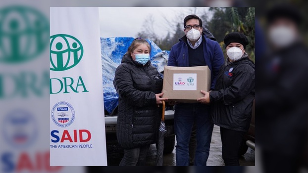 ADRA Chile and USAID staff delivering a hygiene kit. [Photo Credit: ADRA Chile]